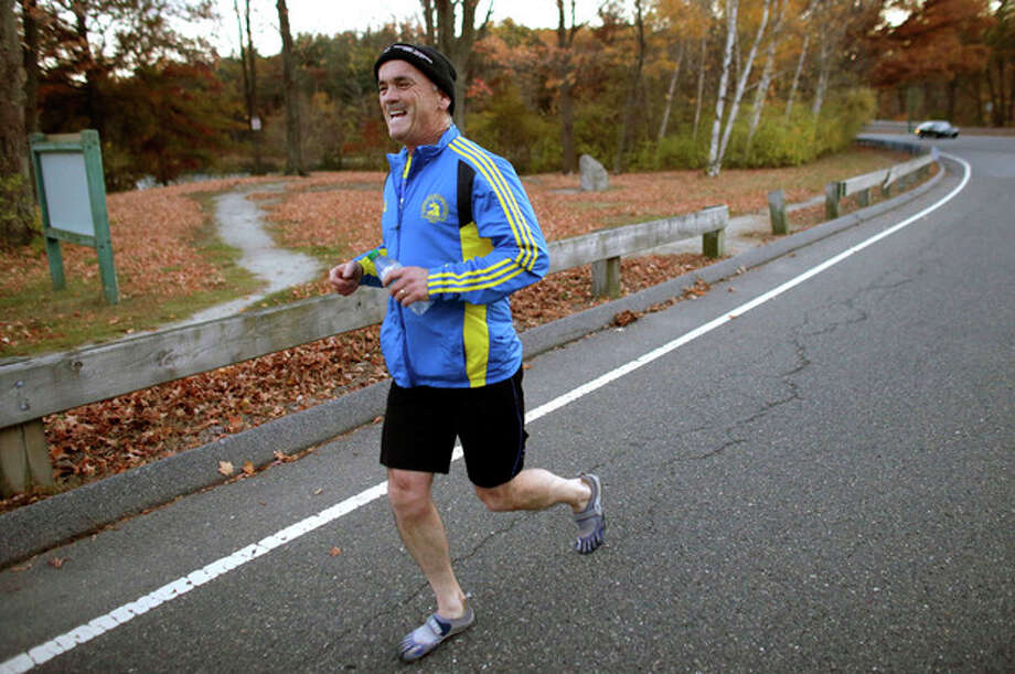 In this photo taken on Tuesday, Oct. 29, 2013, marathon runner Bill McCabe runs along a road in Stoneham, Mass. McCabe was stopped at mile 26 of the Boston Marathon after the April 15, 2013 bombings. He is running the New York Marathon to raise money for six people from his hometown. (AP Photo/Steven Senne) / AP