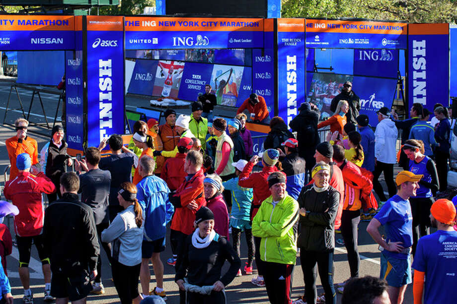 FILE - In this Nov. 3, 2012 file photo, a crowd of runners stands near the barricaded Central Park finish line for the canceled New York Marathon. The increased security will be unmistakable for the Nov. 3, 2013, marathon, from barriers around Central Park to added checkpoints. (AP Photo/ John Minchillo, File) / FR170537 AP