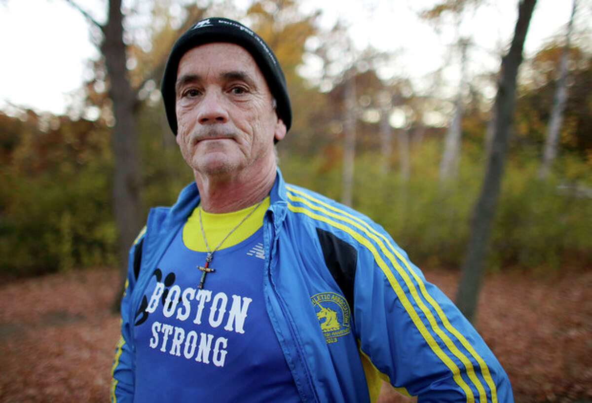 In this photo taken on Tuesday, Oct. 29, 2013, marathon runner Bill McCabe poses for a photo in Stoneham, Mass. McCabe was stopped at mile 26 of the Boston Marathon after the April 15, 2013, bombings. He is running the New York Marathon to raise money for six people from his hometown. (AP Photo/Steven Senne)