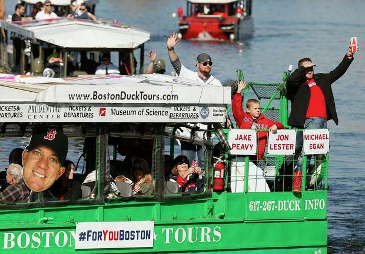 Boston Red Sox's Jon Lester, top center, and Jake Peavy, right, wave from a duck boat on the Charles River during a rolling victory parade celebrating the baseball team's World Series title, Saturday, Nov. 2, 2013, in Boston. (AP Photo/Michael Dwyer