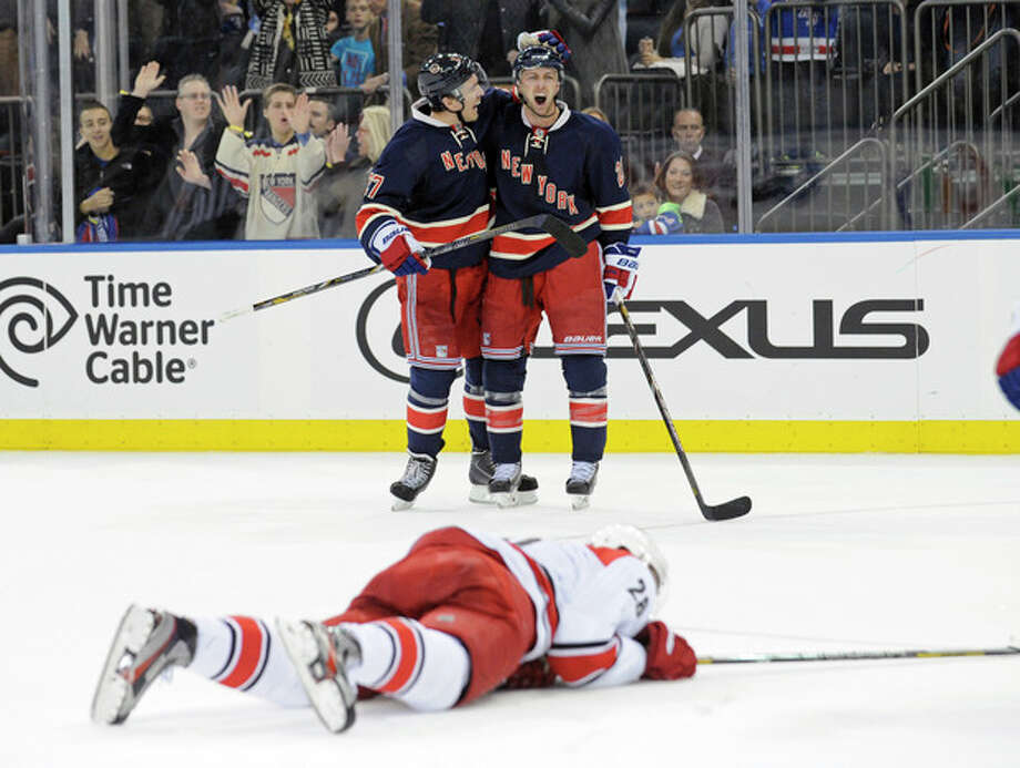 New York Rangers' Derek Stepan, right, celebrates with Ryan McDonagh, left, after Stepan scored a goal, as Carolina Hurricanes' Alexander Semin lies on the ice during the second period of an NHL hockey game Saturday, Nov. 2, 2013, at Madison Square Garden in New York. (AP Photo/Bill Kostroun) / FR51951 AP