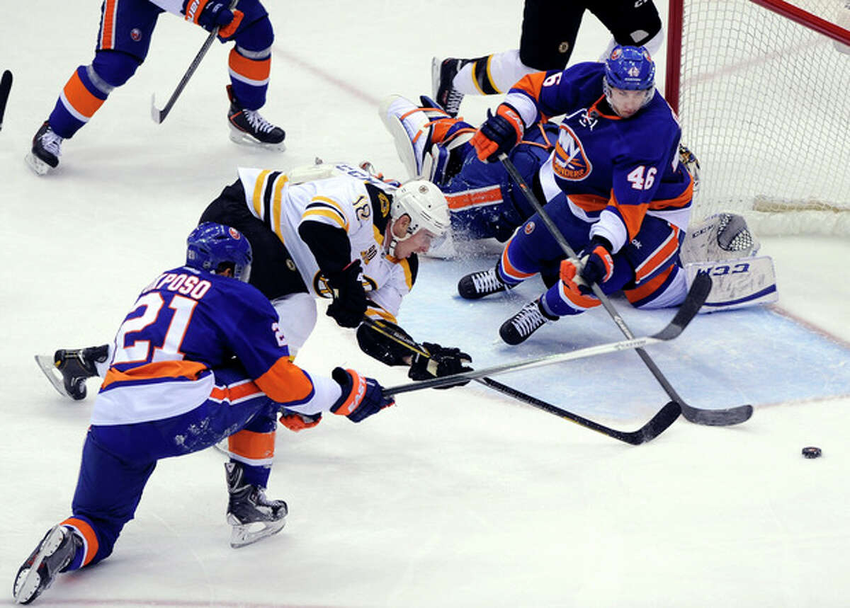 New York Islanders' Kyle Okposo (21) and Matt Donovan (46) block a shot on goal by Boston Bruins' Reilly Smith (18) in the first period of an NHL hockey game at the Nassau Coliseum on Saturday, Nov. 2, 2013, in Uniondale, N.Y. (AP Photo/Kathy Kmonicek)