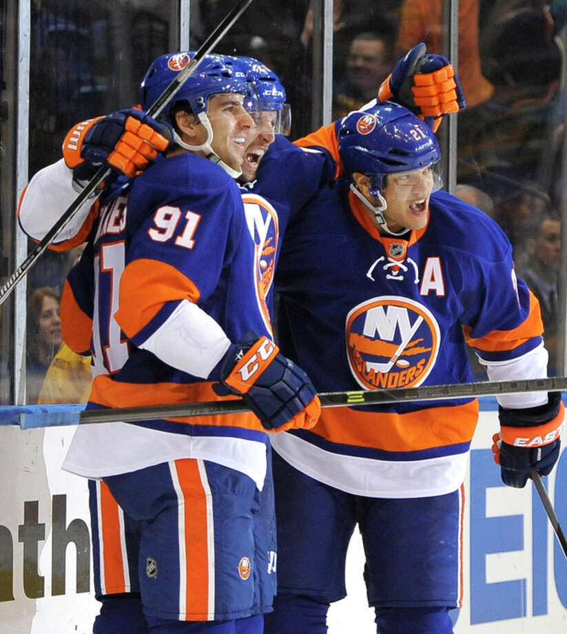 New York Islanders' John Tavares (91), Thomas Vanek, center, and Kyle Okposo (21) celebrate Vanek's first goal as an Islander against the Boston Bruins in the second period of an NHL hockey game at the Nassau Coliseum on Saturday, Nov. 2, 2013, in Uniondale, N.Y. (AP Photo/Kathy Kmonicek) / FR170189 AP