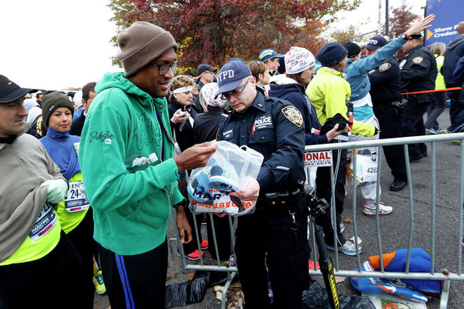 Runners are screened by police officers as they arrive for the New York City Marathon, Sunday, Nov. 3, 2013, in New York. (AP Photo/Jason DeCrow) / FR103966 AP