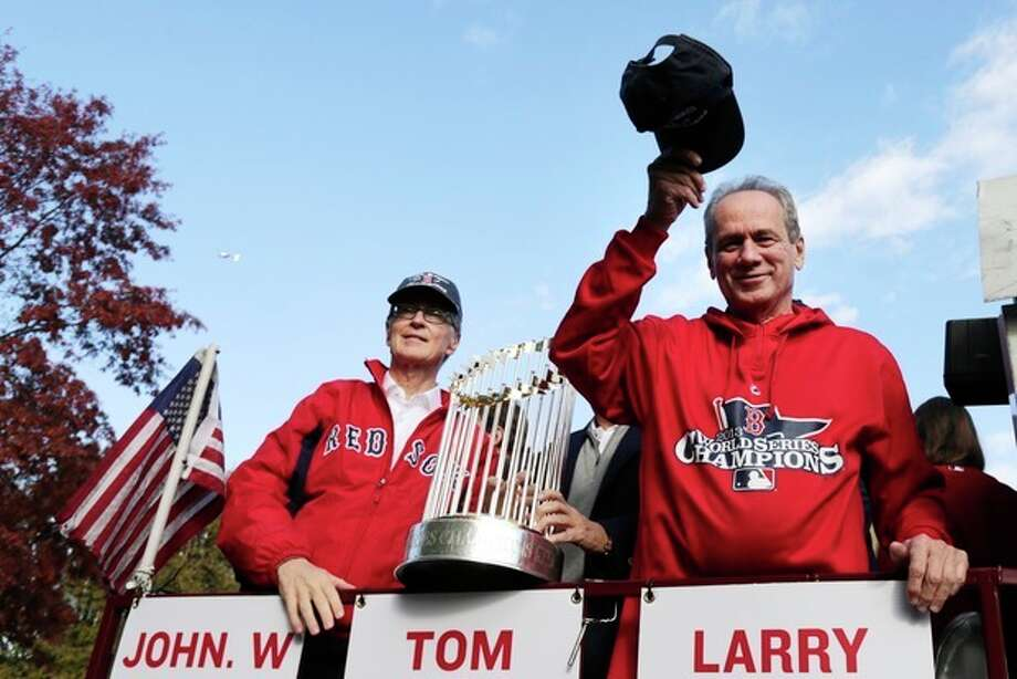 Boston Red Sox president Larry Lucchino, right, tips his cap to fans as majority owner John Henry holds the 2013 World Series championship trophy during a parade in celebration of the baseball team's win, Saturday, Nov. 2, 2013, in Boston. (AP Photo/Charles Krupa) / AP