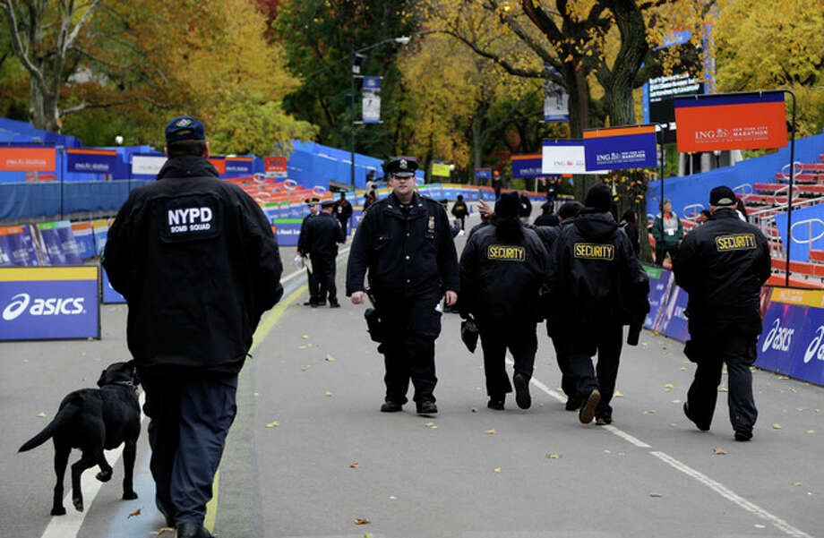 Security personnel walk near the finish line of the 2013 New York City Marathon in New York, Sunday, Nov. 3, 2013. The increased security at the marathon will be most evident near the finish line in Central Park. There will be barricades around the park to limit entry points, bag checks and bomb-sniffing dogs. (AP Photo/Seth Wenig) / AP