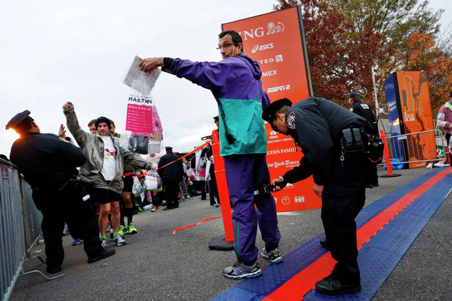 Runners are screened by police officers as they arrive at the start of the New York City Marathon, Sunday, Nov. 3, 2013, in New York. (AP Photo/Jason DeCrow) / FR103966 AP