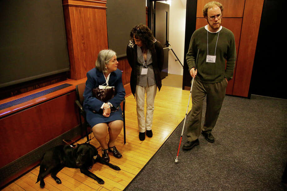 "Anne Donna sits with her guide dog, ""Visa,"" as she talks with volunteer guide Rose Mirakian-Wheeler, center, at a job fair for the visually impaired at Radcliffe Yard in Cambridge, Mass., Thursday, Oct. 24, 2013, as Kyle Robidoux, with the Massachusetts Association for the Blind and Visually Impaired, walks by. (AP Photo/Stephan Savoia) / AP"