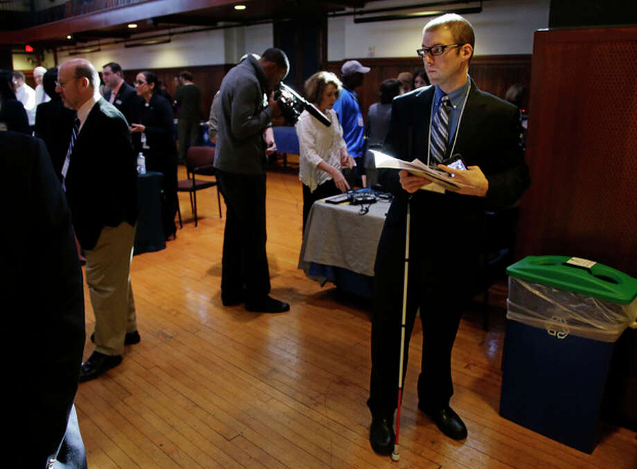 Jeff Paquette, right, a graduate of Johnson and Wales University, attends a job fair for the visually impaired on the Radcliffe Yard campus in Cambridge, Mass., Thursday, Oct. 24, 2013. Declared legally blind in 2006, he has limited vision that prevents him from driving but enables him to use public transportation on his own and to read, sometimes with the help of a magnification option on his computer. (AP Photo/Stephan Savoia) / AP