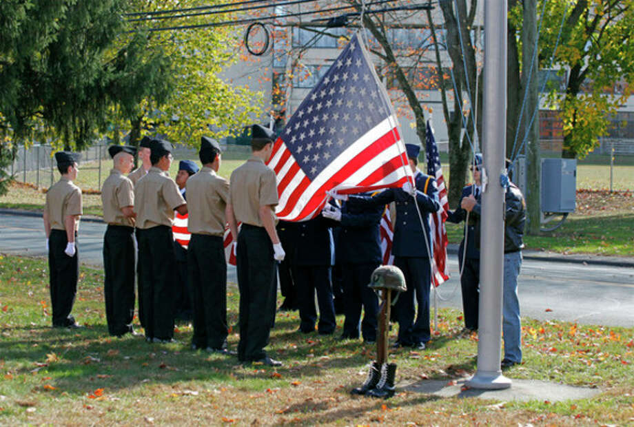 A flag is raised during the American Legion Hall's Veteran of the Month ceremony Sunday morning.Hour Photo / Danielle Calloway