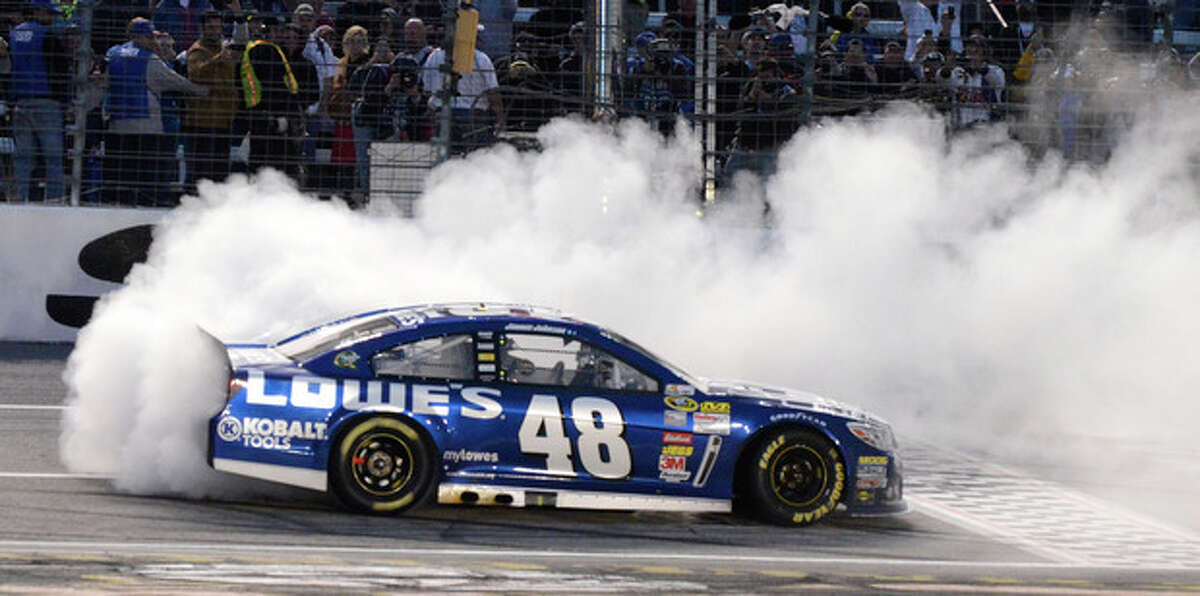 Jimmie Johnson (48) burns his tires after winning the NASCAR Sprint Cup series auto race at Texas Motor Speedway in Fort Worth, Texas, Sunday, Nov. 3, 2013. (AP Photo/Larry Papke)