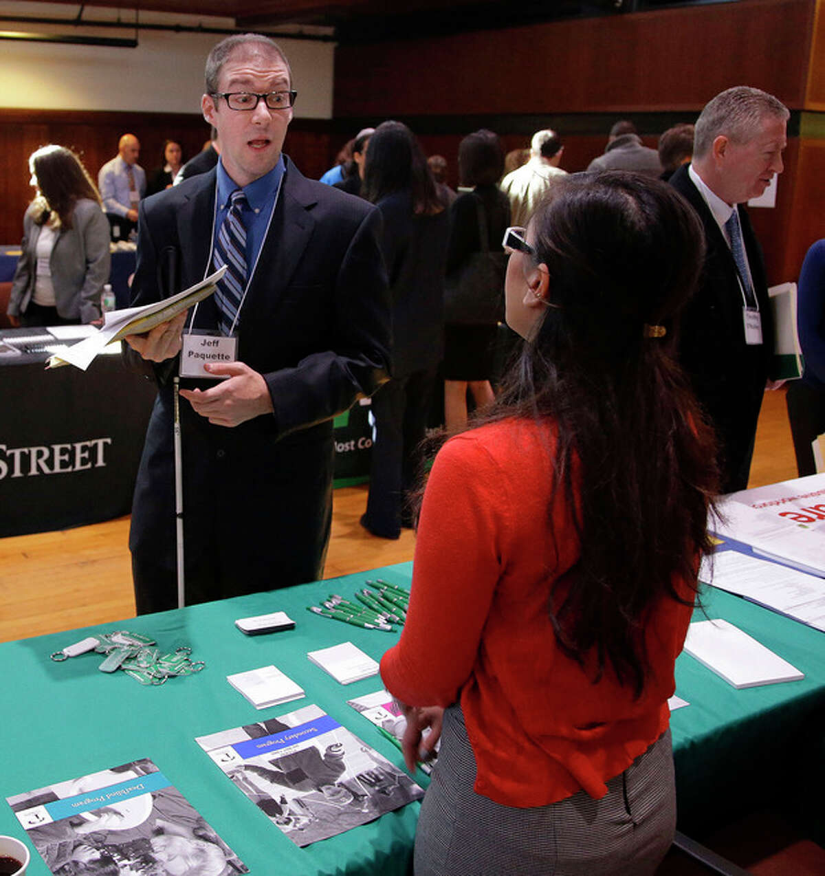Jeff Paquette, left, a graduate of Johnson and Wales University, speaks to a recruiter during a job fair for the visually impaired on the Radcliffe Yard campus in Cambridge, Mass., Thursday, Oct. 24, 2013. Paquette, who is searching for a position in the hospitality industry, says