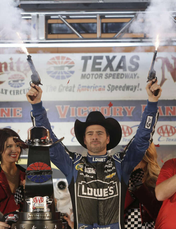 Jimmie Johnson fires pistols to celebrate winning the NASCAR Sprint Cup series auto race at Texas Motor Speedway in Fort Worth, Texas, Sunday, Nov. 3, 2013. (AP Photo/Brandon Wade)