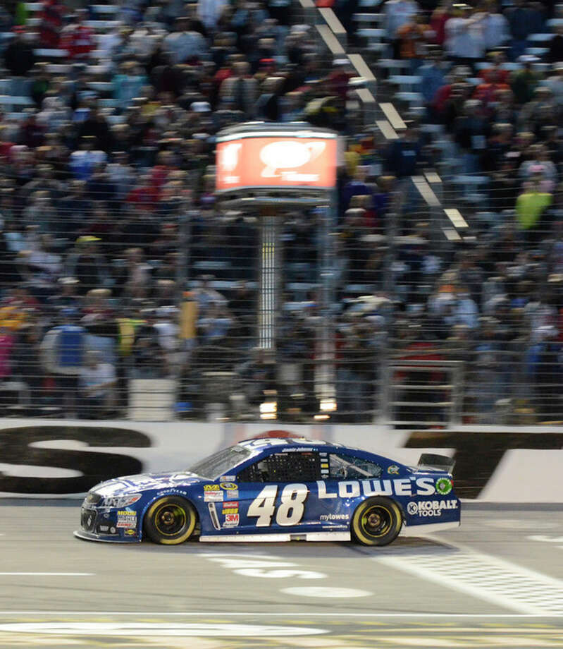 Jimmie Johnson (48) crosses the finish line winning the NASCAR Sprint Cup series auto race at Texas Motor Speedway in Fort Worth, Texas, Sunday, Nov. 3, 2013. (AP Photo/Larry Papke) / FR58581 AP