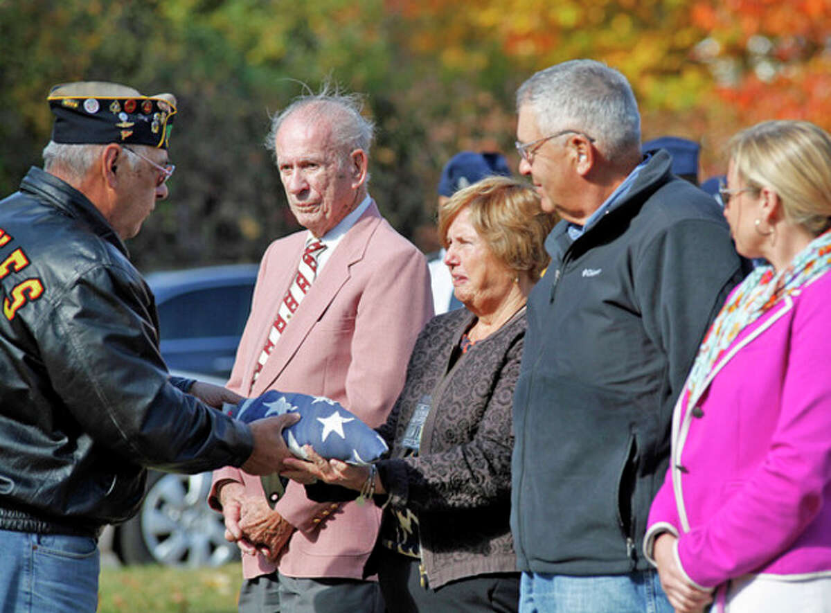 @Cutline Byline:Hour Photos / Danielle Calloway Above, Dhruvil Shah of Brien McMahon's NJROTC salutes during the American Legion Hall's Veteran of the Month ceremony Sunday morning. At right, a flag is presented to Eileen Iannazzi.