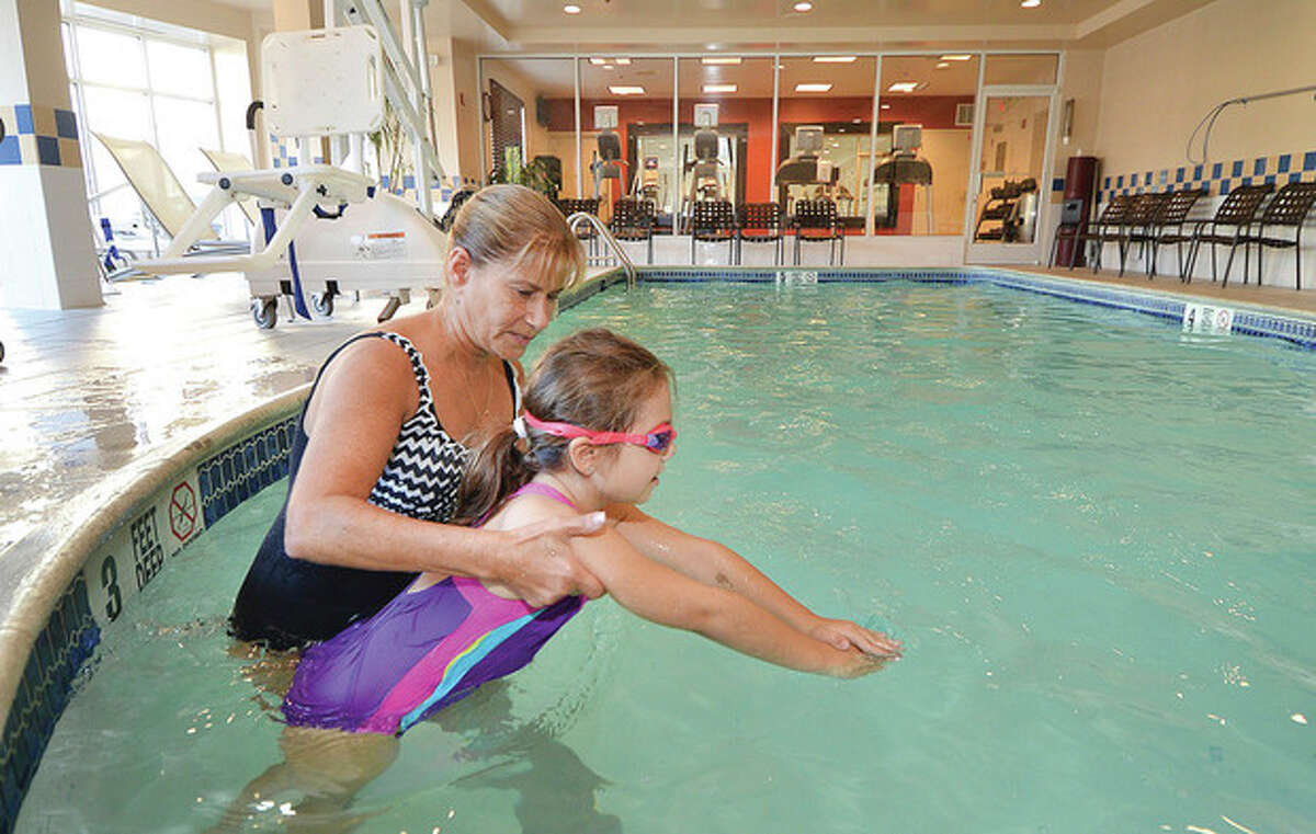 Hour Photo/Alex von Kleydorff Instructor Kathy Tavella helps 7yr old Ella Trivisonno with some movements for breast stroke at the pool in The Hilton Garden Inn