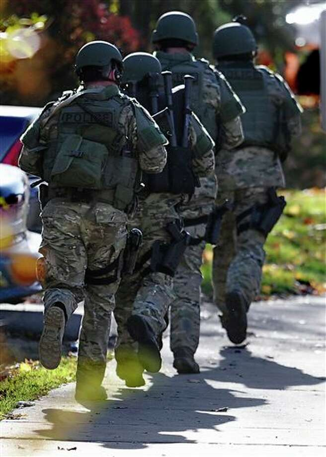 "SWAT move in a line on the campus of Central Connecticut State University, Monday, Nov. 4, 2013, in New Britain, Conn. An armed man was spotted on the campus of Central Connecticut State University, prompting a schoolwide lockdown and warnings for students to stay away from windows as police SWAT teams swarmed the area. University spokesman Mark McLaughlin said, ""Somebody was seen either with a gun or was thought to have a gun."" / AP2013"
