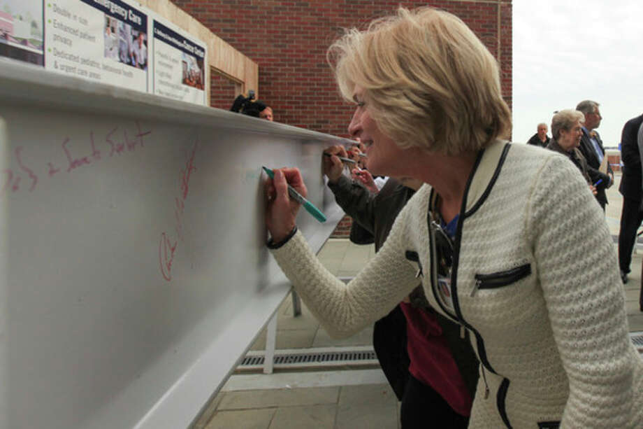 Hour Photo / Chris Palermo. Norwalk Hospital Employee Cathy Coyle signs the beam at the beam signing reception for all donors who contributed to the Legacy of Caring capital campaign at Norwalk Hospital Tuesday afternoon. Donors were invited to leave their mark on Norwalk Hospital's history by signing the large steel beam that be used to support the new pavilion entrance. / © 2013 Hour Newspapers All Rights Reserved