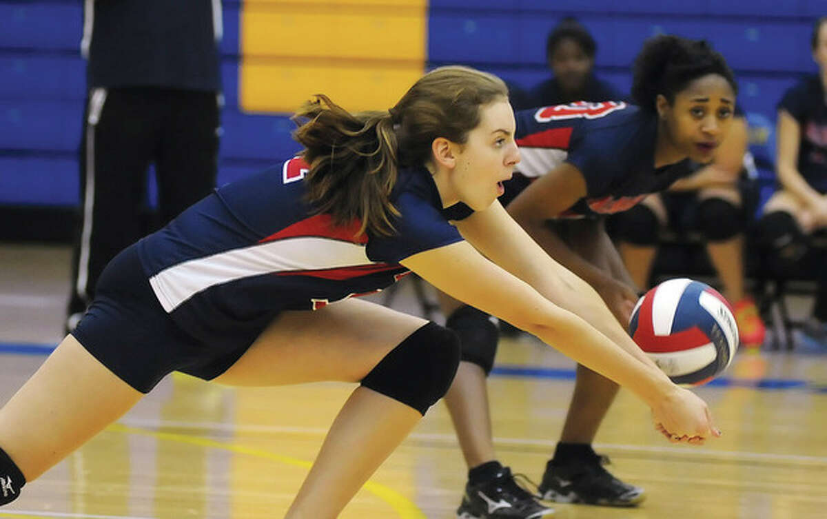 Hour photo/John Nash Brien McMahon's Claire Kostohryz, left, goes for a bump as teammate Sarah Boyd looks on during Monday's state tournament match against Newtown.