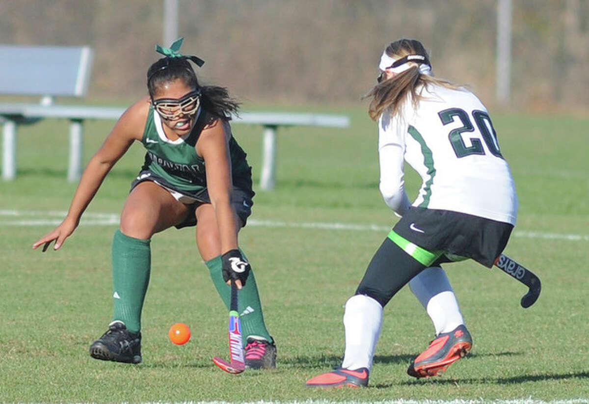 Hour photo/John Nash Norwalk's Sara Meza, left, deflects the ball after it was hit by New Milford's Taylor Duffany during Monday's Class LL preliminary playoff game at New Milford. Duffany scored the game's only goal in New Milford 1-0 win.