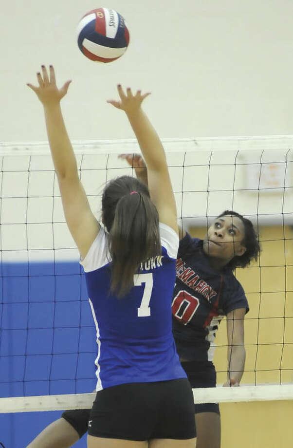 Hour photo/John NashBrien McMahon's Sarah Boyd, right, spikes the ball over the head of Newtown blocker Meghan Logan.