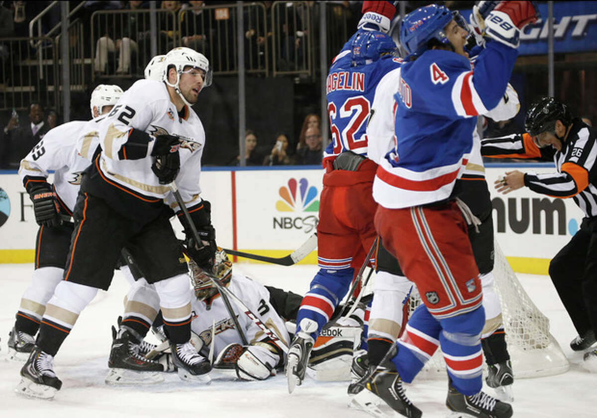 Anaheim Ducks left wing Patrick Maroon (62) watches as New York Rangers defenseman Michael Del Zotto (4) and Rangers left wing Carl Hagelin (62) of Sweden react after Del Zotto scored a goal in the second period of their NHL hockey game at Madison Square Garden in New York, Monday, Nov. 4, 2013. (AP Photo/Kathy Willens)