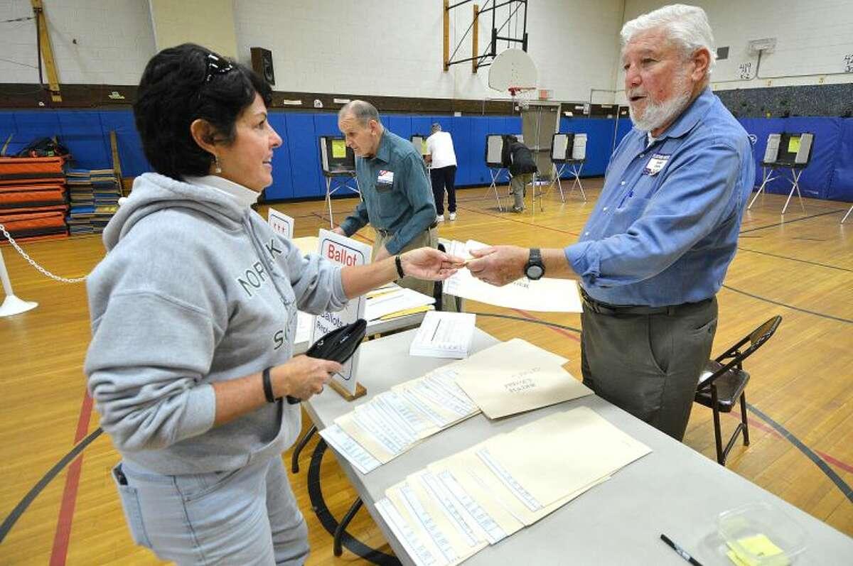 Hour Photo/Alex von Kleydorff Ballot Clerk Fred Edelman hands a privacy folder to Sharon Cadden during election day voting at Marvin School.