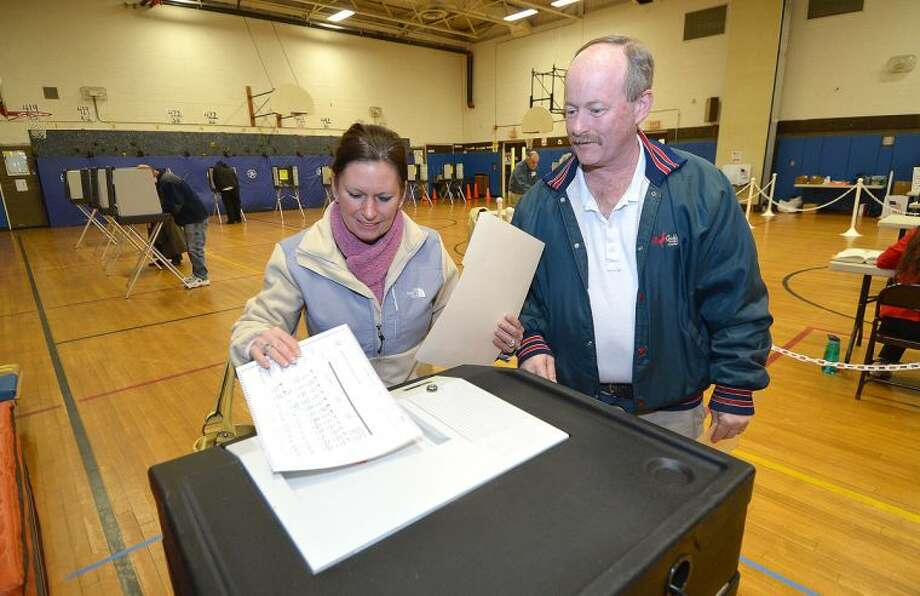 Hour Photo/Alex von Kleydorff . Tina and husband Joe Gallo cast their votes at the Marvin School on election day in Norwalk