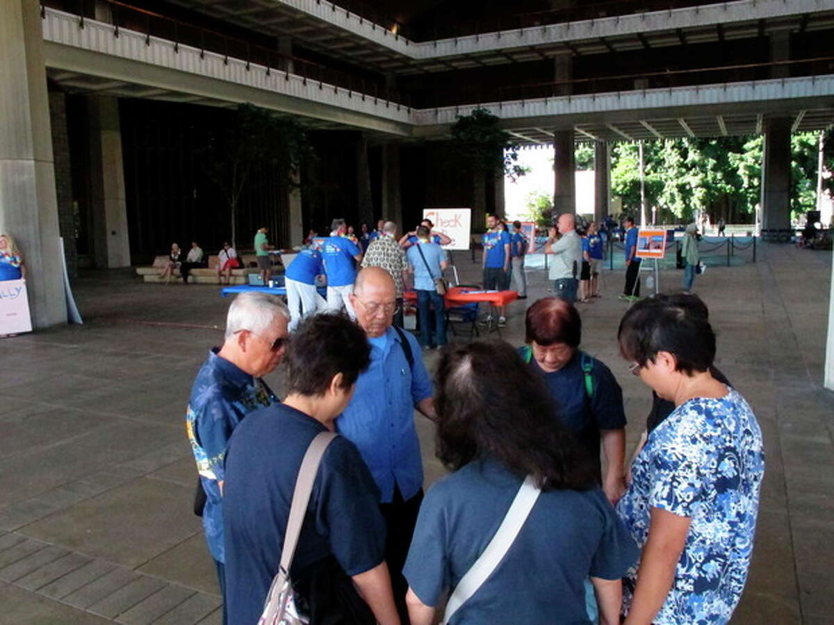 Members of the Hawaii Chinese Baptist Church pray outside on the Hawaii Capitol rotunda before a joint House committee hearing on gay marriage in Honolulu on Thursday, Oct. 31, 2013. (AP Photo/Oskar Garcia)