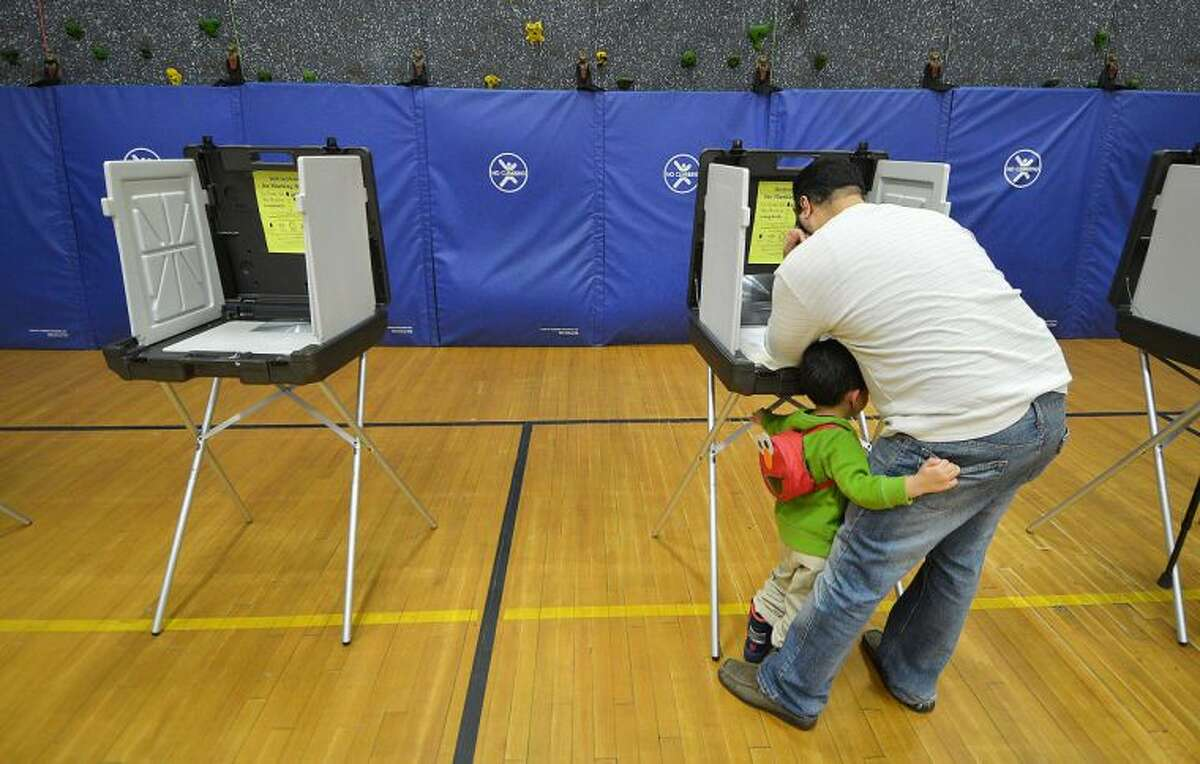 Hour Photo/Alex von Kleydorff 4 yr old Yassin El-Yamani hangs on to his father Jimmy's back pocket as he votes on Election day at The Marvin School.