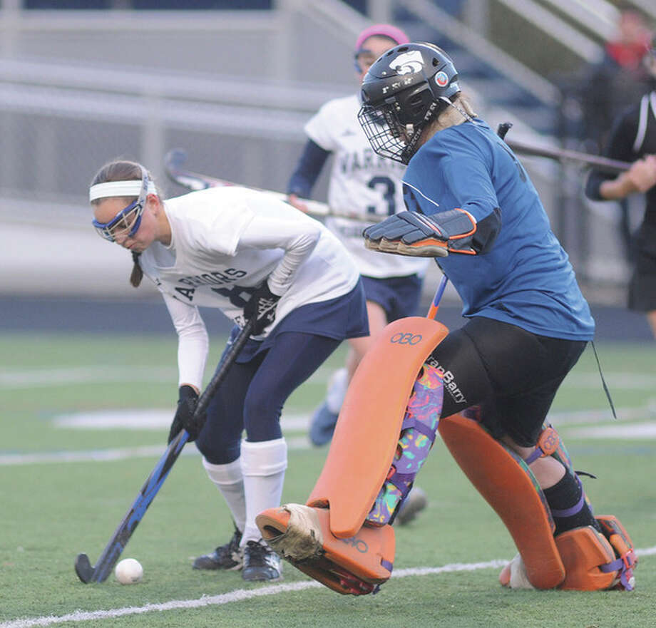 Hour photo/John NashWilton's Kristen Godin, left, carries the ball around Masuk goaltender Brooke Upton during Tuesday's Class M state tournament game at Wilton.