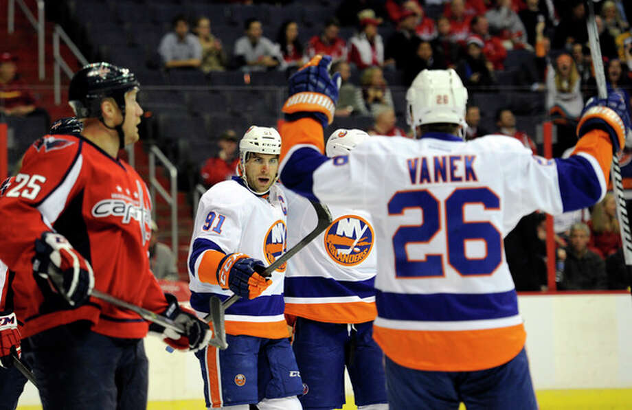 New York Islanders center John Tavares (91) celebrates his goal with teammate Thomas Vanek (26), of Austria, and others as Washington Capitals left wing Jason Chimera (25) skates by during the first period an NHL hockey game, Tuesday, Nov. 5, 2013, in Washington. (AP Photo/Nick Wass) / FR67404 AP