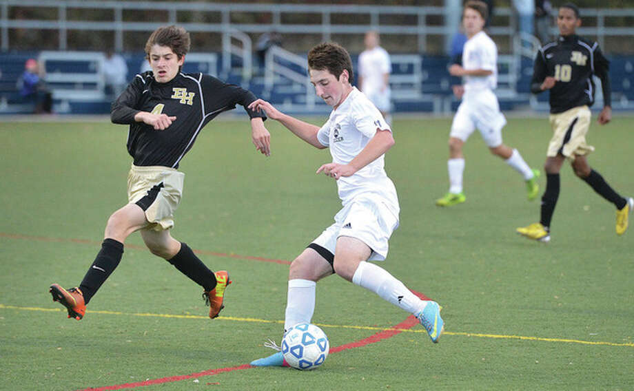 Hour photo/Alex von KleydorffWilton's Justin Shepard, right, lines up the ball as an East Hartford defender closes in during Tuesday's state tournament game in Wilton. The Warriors moved on after claiming a 1-0 victory.