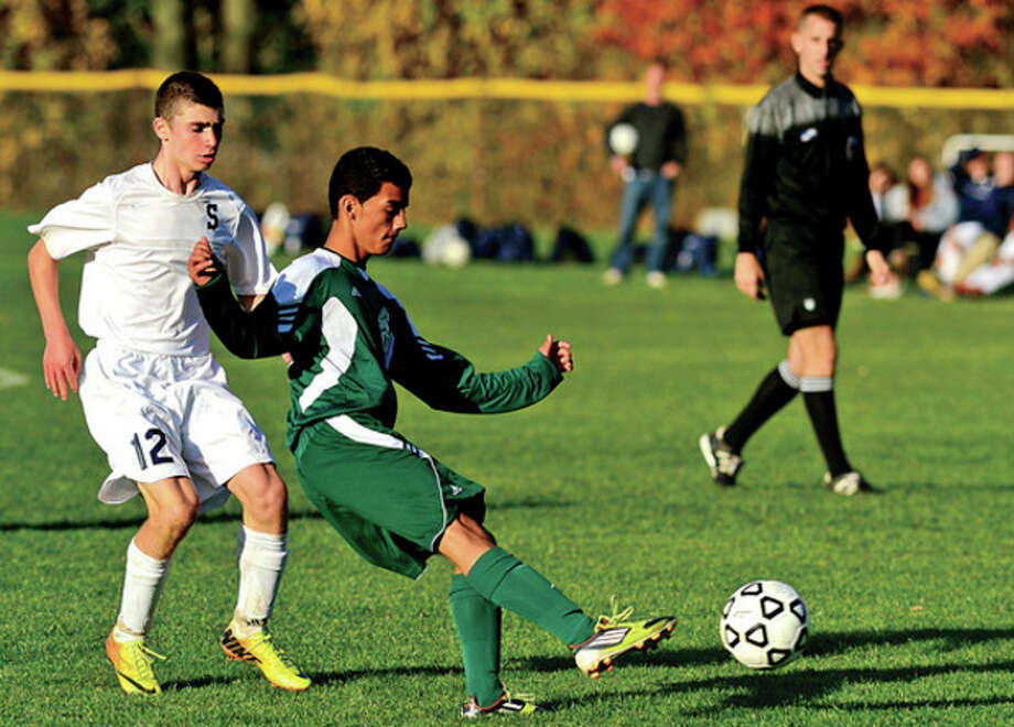 Hour photo/Erik TrautmannJoe Pravder of Staples, left, and Norwalk's Jon Ceja battle for the ball during Tuesday's Class LL state tournament game in Westport. Pravder scored the game's only goal on a blast with 1:39 remaining in the game, allowing the Wreckers to take a 1-0 victory and advance to the second round. / (C)2013, The Hour Newspapers, all rights reserved