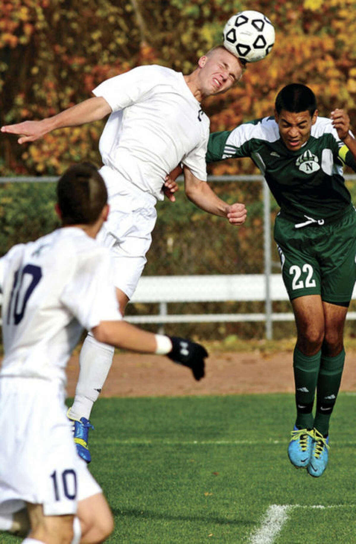 Hour photo/Erik Trautmann Andrew Puchala of Staples outjumps Norwalk's Sergio Mandujano for a header during Tuesday's Class LL state tournament game in Westport. Diego Alanis (10) of Staples gets a close look at the play. The Wreckers advanced with a 1-0 victory over the visiting Bears, the defending Class LL champs.