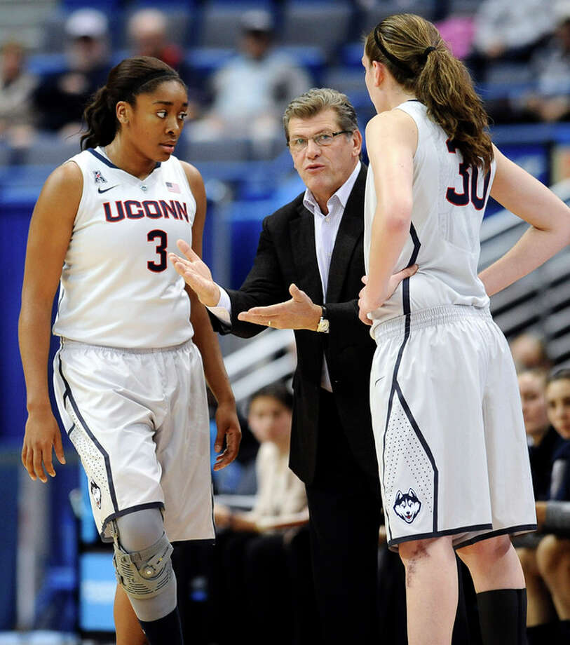Connecticut coach Geno Auriemma, center talks with players Morgan Tuck, left, and Breanna Stewart during the first half of an NCAA college exhibition basketball game against Philadelphia, Tuesday, Nov. 5, 2013, in Hartford, Conn. (AP Photo/Jessica Hill) / FR125654 AP