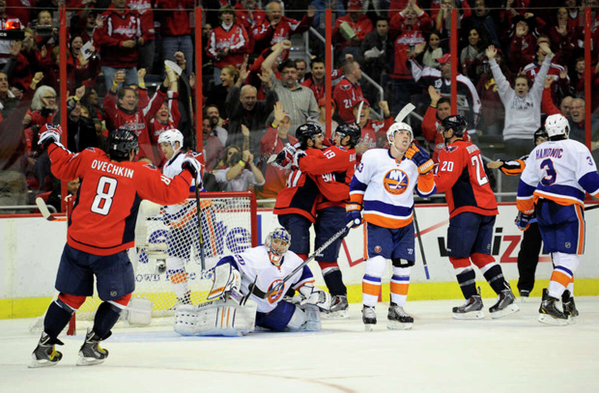 Washington Capitals center Marcus Johansson (90), of Sweden, celebrates his goal with Nicklas Backstrom (19), also of Sweden, Alex Ovechkin (8), of Russia, and Troy Brouwer (20) as New York Islanders goalie Evgeni Nabokov, center, of Kazakhstan, looks on during the second period an NHL hockey game, Tuesday, Nov. 5, 2013, in Washington. Also seen are New York Islanders center Casey Cizikas (53) and Travis Hamonic (3). (AP Photo/Nick Wass)