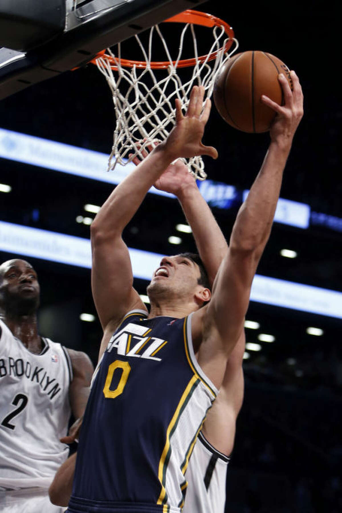 Utah Jazz's Enes Kanter (0)goes to the basket against the Brooklyn Nets' Kevin Garnett (2) and Brook Lopez during the first half of an NBA basketball game Tuesday, Nov. 5, 2013, in New York. (AP Photo/Jason DeCrow)