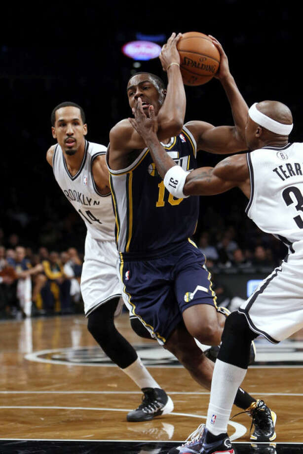 Utah Jazz's Alec Burks (10) drives between Brooklyn Nets' Shaun Livingston, left, and Jason Terry during the first half of an NBA basketball game Tuesday, Nov. 5, 2013, in New York. (AP Photo/Jason DeCrow)