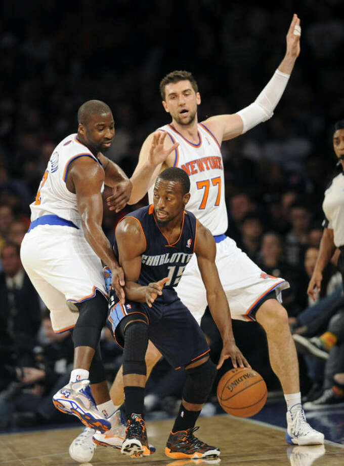 Charlotte Bobcats' Kemba Walker is pressured by New York Knicks' Raymond Felton, left, and Andrea Bargnani (77), of Italy, during the first quarter of an NBA basketball game Tuesday, Nov. 5, 2013, at Madison Square Garden in New York. (AP Photo/Bill Kostroun)
