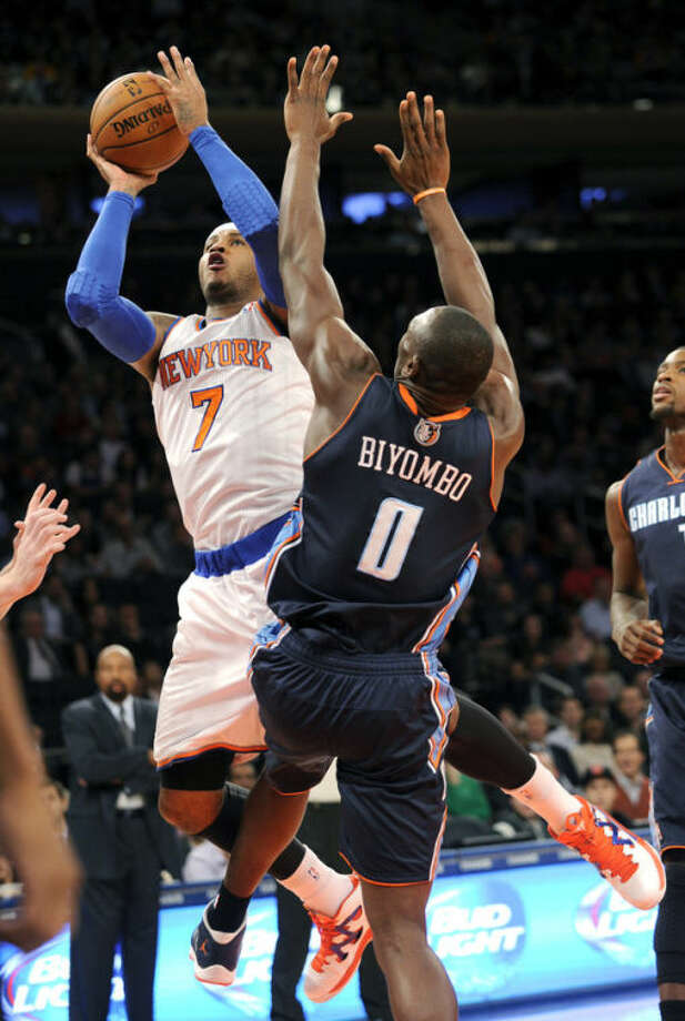 New York Knicks' Carmelo Anthony, left, puts up a shot shsindy Charlotte Bobcats' Bismack Biyombo during the first quarter of an NBA basketball game Tuesday, Nov. 5, 2013, at Madison Square Garden in New York. (AP Photo/Bill Kostroun)