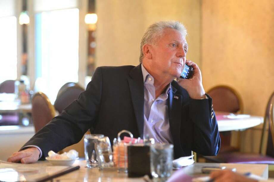Hour Photo/Alex von Kleydorff . Mayor Elect Harry Rilling takes a phone call while talking to The Hour at Penny's diner, the day after being elected.