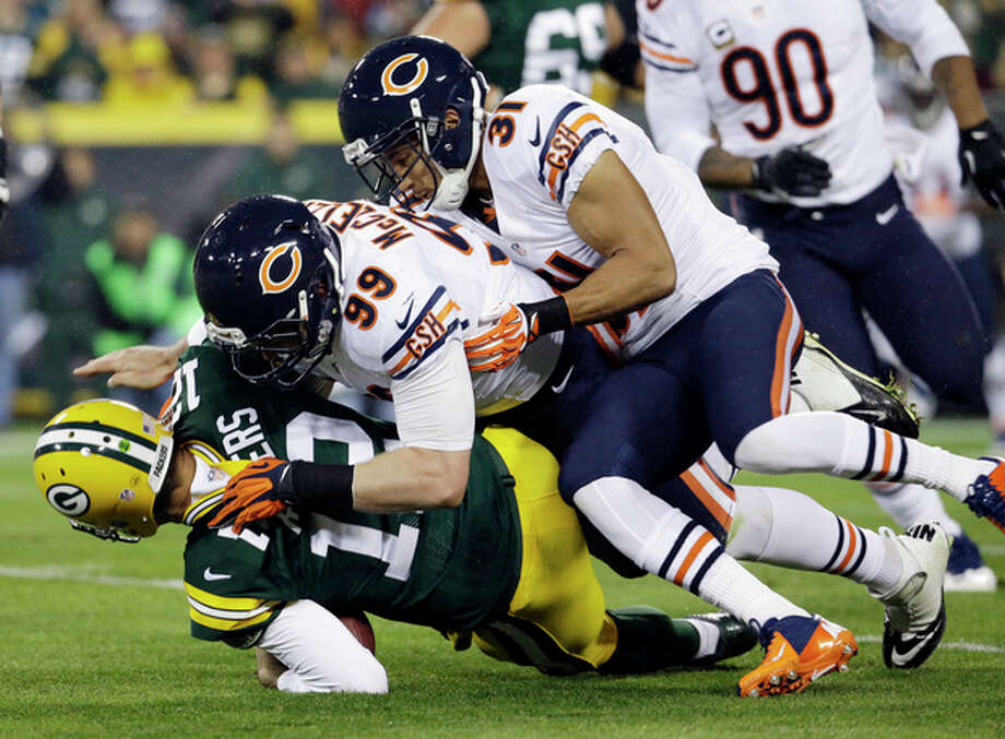 Green Bay Packers quarterback Aaron Rodgers is sacked by Chicago Bears' Shea McClellin (99) and Isaiah Frey (31) during the first half of an NFL football game Monday, Nov. 4, 2013, in Green Bay, Wis. (AP Photo/Morry Gash) / AP