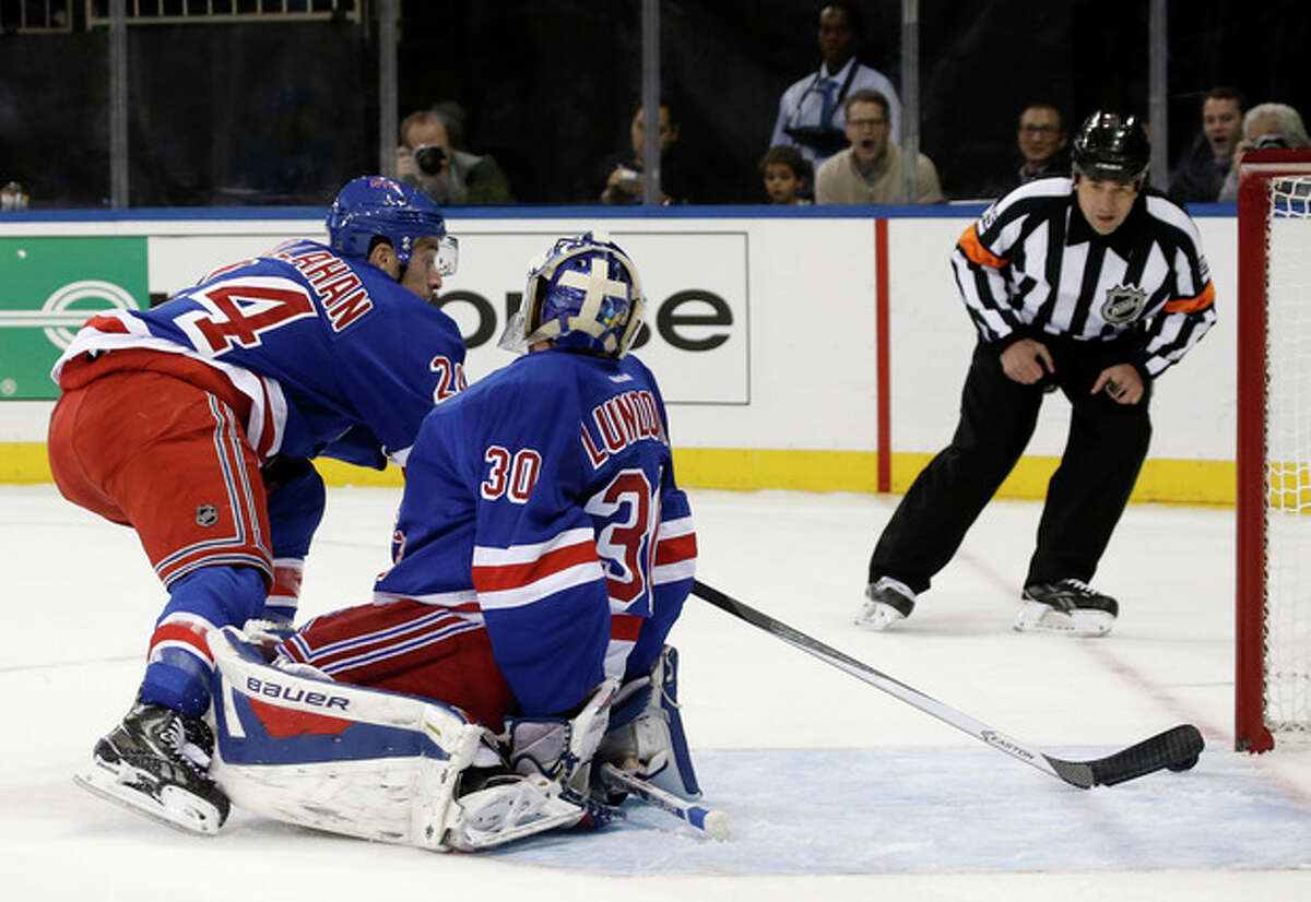 New York Rangers right wing Ryan Callahan (24) knocks the puck away from the goal behind Rangers goalie Henrik Lundqvist (30) during the first period of an NHL hockey game against the Pittsburgh Penguins at Madison Square Garden in New York, Wednesday, Nov. 6, 2013. (AP Photo/Kathy Willens)