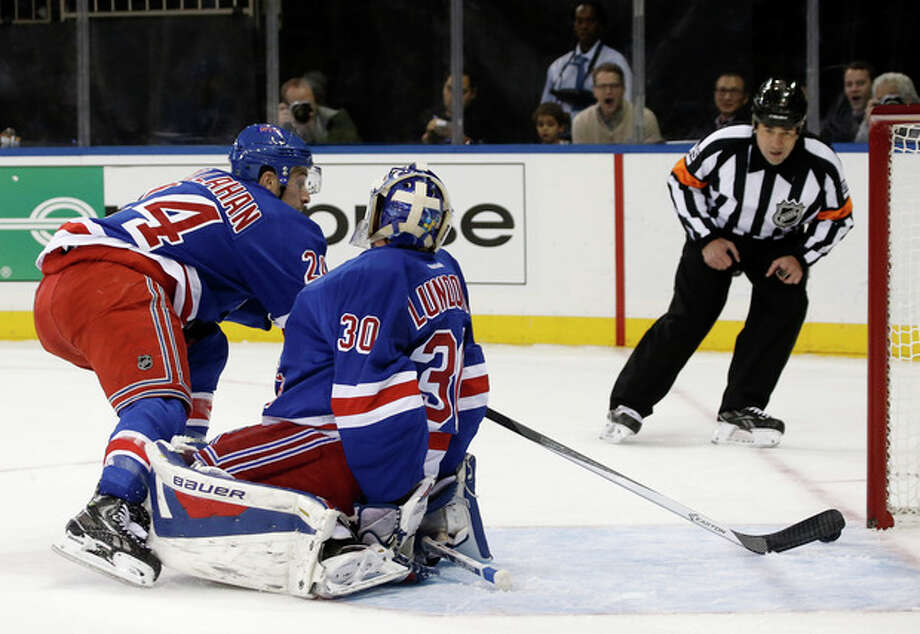 New York Rangers right wing Ryan Callahan (24) knocks the puck away from the goal behind Rangers goalie Henrik Lundqvist (30) during the first period of an NHL hockey game against the Pittsburgh Penguins at Madison Square Garden in New York, Wednesday, Nov. 6, 2013. (AP Photo/Kathy Willens) / AP
