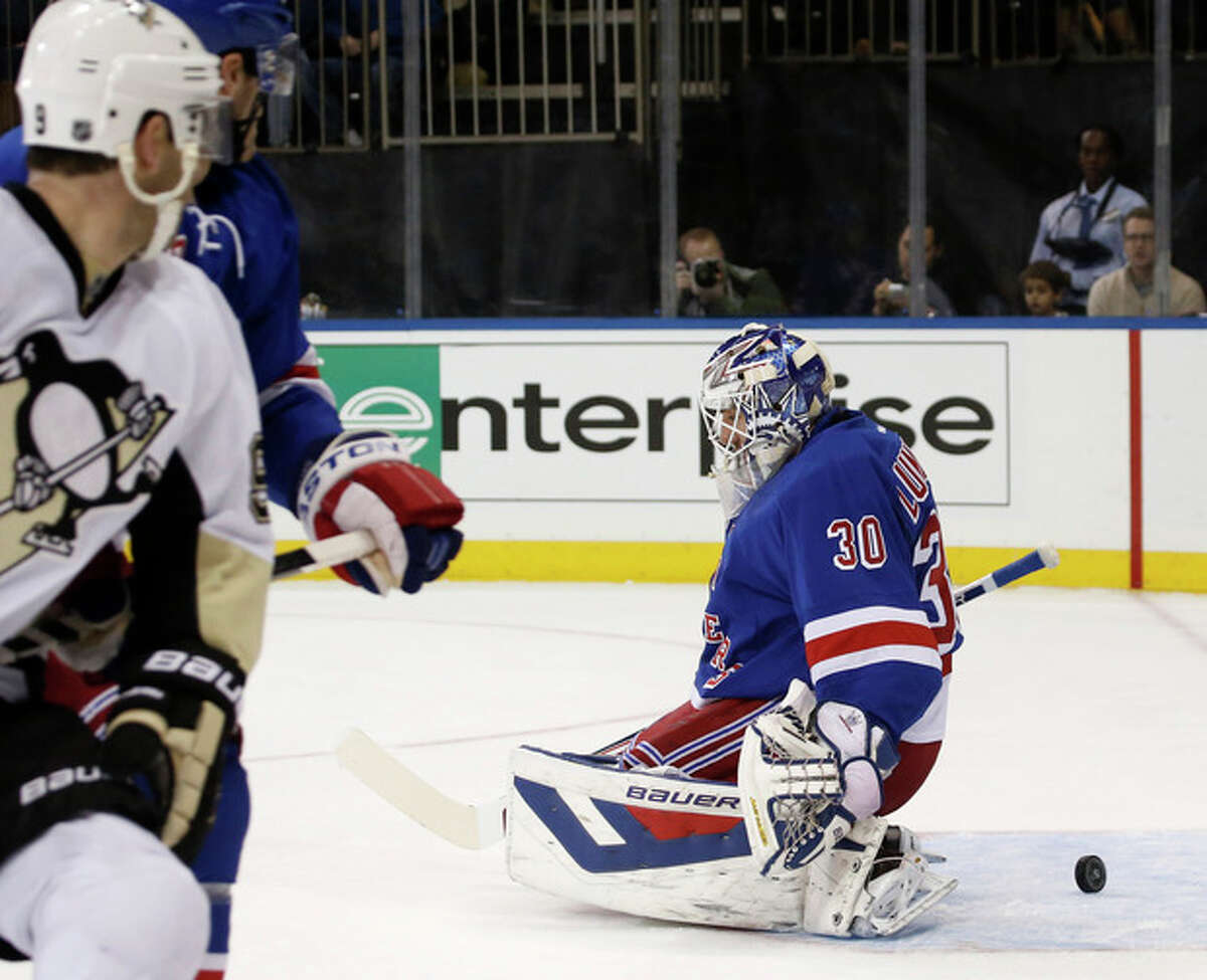 The puck slides behind New York Rangers goalie Henrik Lundqvist (30), who made a save in the first period of their NHL hockey game against the Pittsburgh Penguins at Madison Square Garden in New York, Wednesday, Nov. 6, 2013. (AP Photo/Kathy Willens)