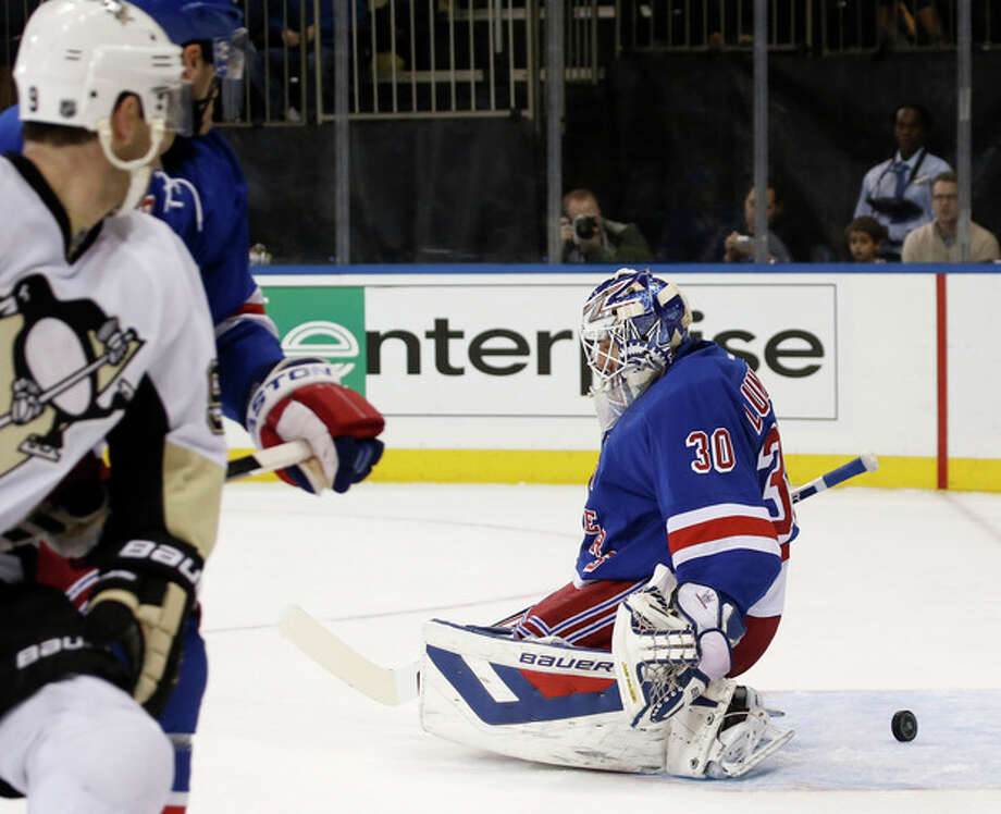 The puck slides behind New York Rangers goalie Henrik Lundqvist (30), who made a save in the first period of their NHL hockey game against the Pittsburgh Penguins at Madison Square Garden in New York, Wednesday, Nov. 6, 2013. (AP Photo/Kathy Willens) / AP