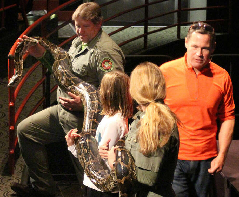 Hour photo / Chris Bosak Television host, biologist and conservationist Jeff Corwin talks to the crowd as professional reptile handlers and young volunteers hold a Burmese python during Corwin's program at the Maritime Aquarium at Norwalk on Wednesday afternoon.