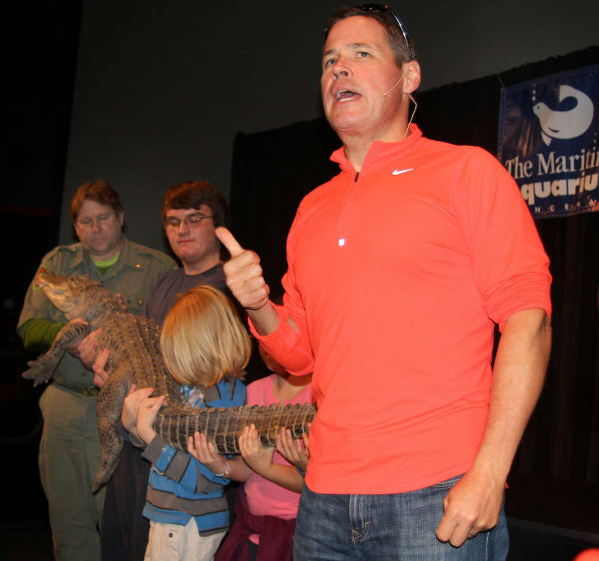 Hour photo / Chris Bosak Television host, biologist and conservationist Jeff Corwin talks to the crowd as professional reptile handlers and young volunteers hold an American alligator during Corwin's program at the Maritime Aquarium at Norwalk on Wednesday afternoon.