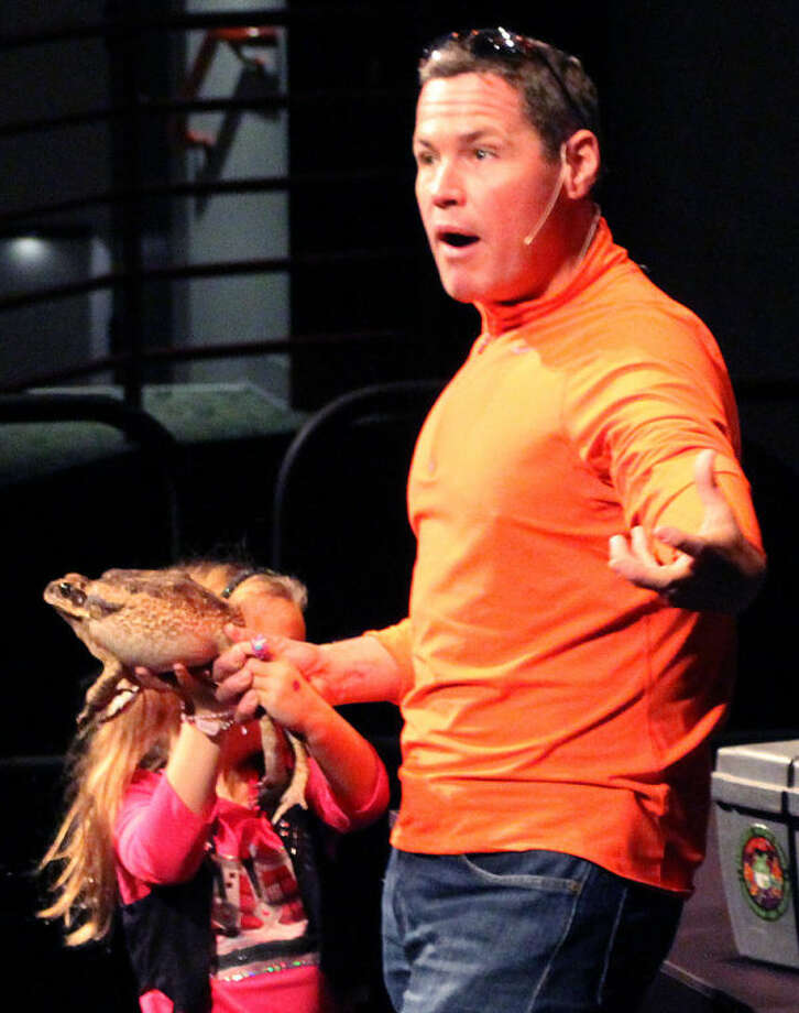 Hour photo / Chris Bosak Television host, biologist and conservationist Jeff Corwin talks to the crowd as a young volunteer holds a marine toad during Corwin's show at the Maritime Aquarium at Norwalk on Wednesday.